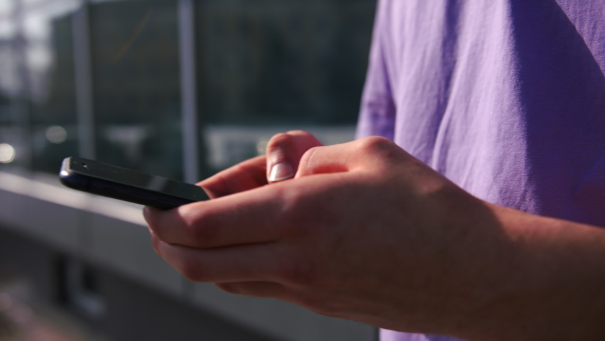 A close-up of a hand with a phone surfing the Internet is a modern concept. In the background is a house with large glass windows Royalty-Free Stock Footage #1068157355