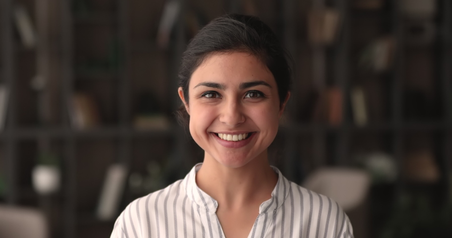 Head shot portrait of smiling beautiful millennial indian mixed race businesswoman looking at camera, showing self confidence, youth multiracial generation female representative, career concept.