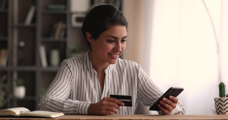 Happy millennial indian ethnicity woman holding bank card, entering cvv code or payment information in mobile internet shopping application, feeling amazed of purchasing goods or services online. Royalty-Free Stock Footage #1068157376