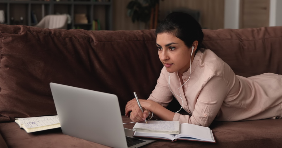 Concentrated millennial indian woman in wired earphones lying on sofa with books and laptop, involved in watching educational online lecture, improving knowledge distantly, e-learning concept. | Shutterstock HD Video #1068159977