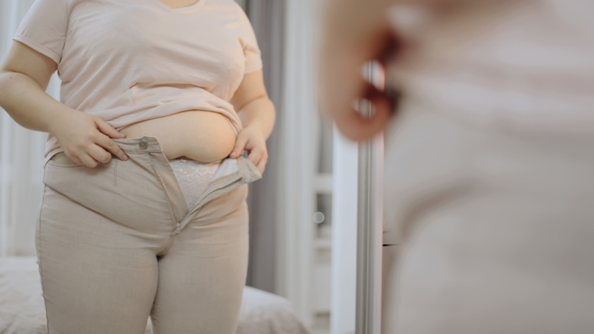 Oversize woman zipping up trousers, excess belly fat, unhealthy lifestyle, diet Royalty-Free Stock Footage #1068162359