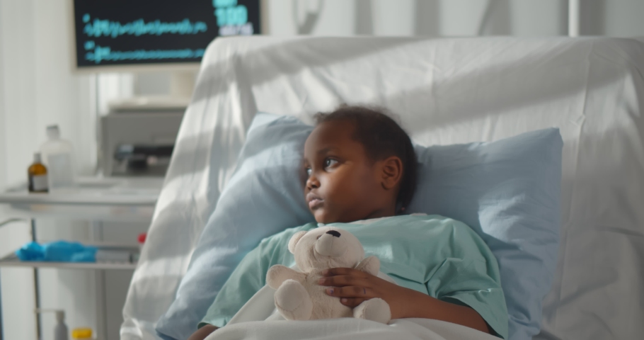 Portrait of sick african girl hugging teddy bear lying in hospital bed. Ill and sad afro-american child patient resting in intensive care unit at modern pediatrics department Royalty-Free Stock Footage #1068162743