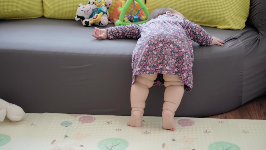 Authentic close up shot of funny sleepy newborn baby kid in dress indoors. Happy child want to sleep lay down on sofa playing with mom at home. infant, family, childhood, life, authenticity concept Royalty-Free Stock Footage #1068166739