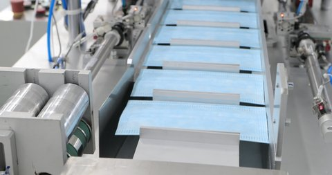 Covid protection. Manufacture of respiratory face masks. Medical mask on conveyor belt in the workshop of medicine factory. Production of disposable medical clothing for protection against the virus.