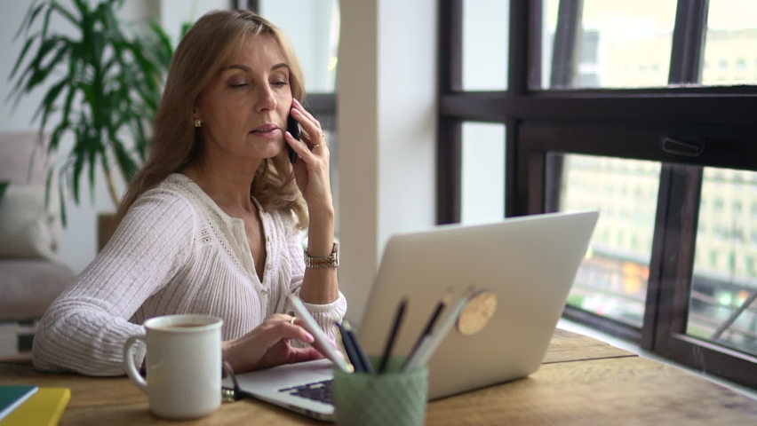 Mature business woman working on laptop and smartphone. Discuss business issues on phone. Female entrepreneur sit in office and talk with colleague, coworker. Concept computer