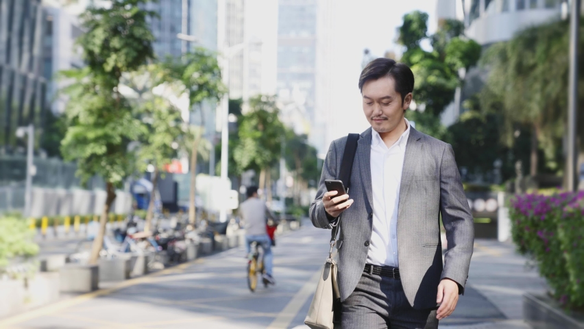 Asian business man walking on street in modern city   Shutterstock HD Video #1068216386