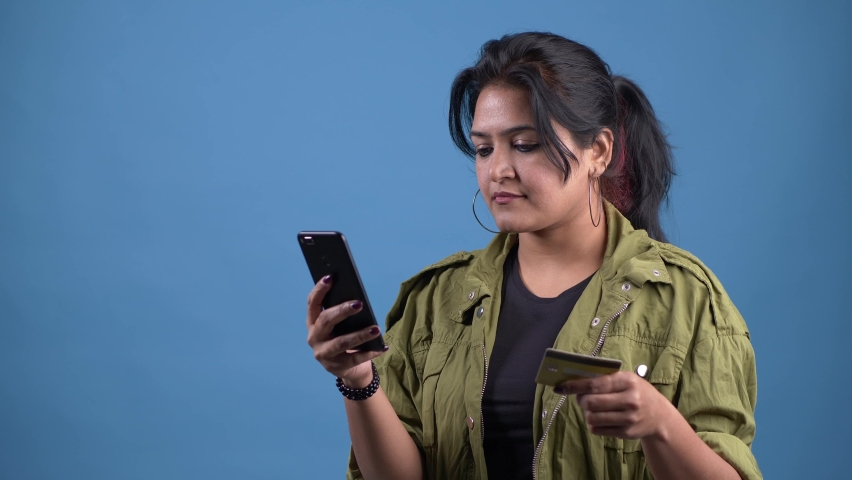 Happy young Asian woman holding credit card using instant mobile payments at studio.Smiling beautiful girl customer shopper making purchase on smart phone receiving cashback concept.E-banking service. Royalty-Free Stock Footage #1068219167