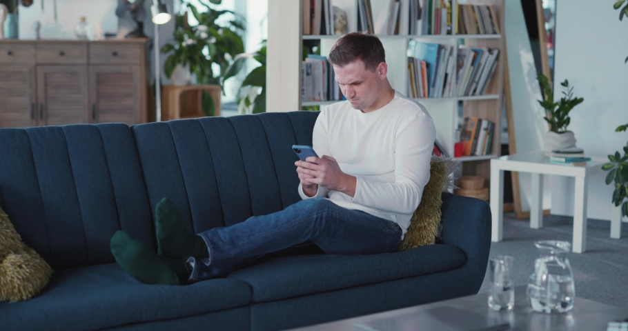 Young manusing smartphone in living room casual modern apartment texting messages netowkring on social media pps indoors. Royalty-Free Stock Footage #1068224807