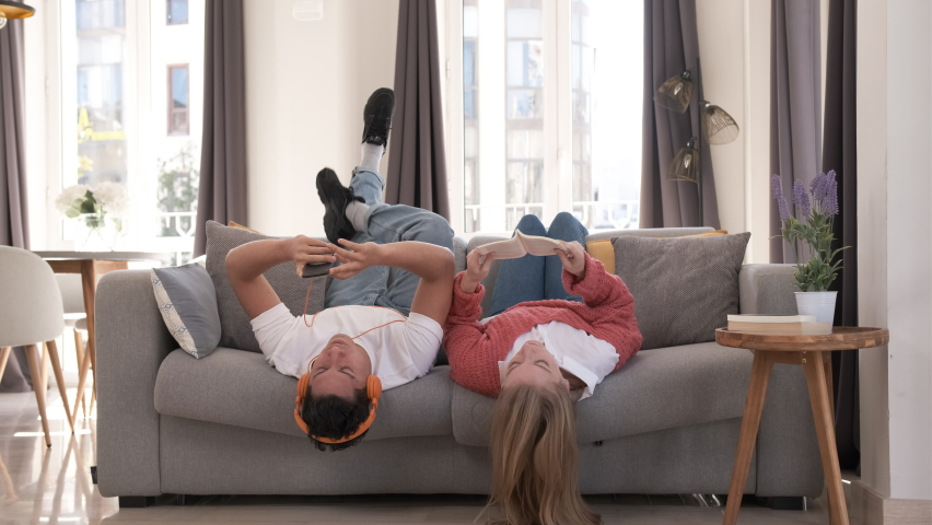 Young couple relaxing and spending time together while laying on the couch at home. | Shutterstock HD Video #1068259934