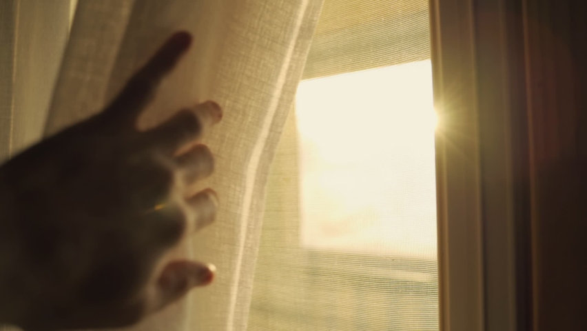 Hand reaches towards a window lit by sunlight - moves curtain to reveal the sun. Sunrise or sunset behind the window. Slow motion move to peek outside. Symbol of hope positivity and energy Royalty-Free Stock Footage #1068260495