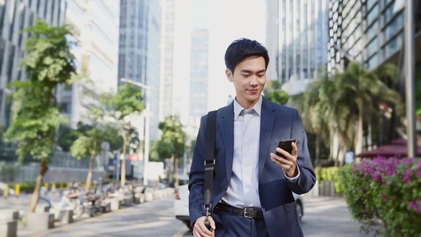 Young asian business man looking at cellphone while walking on street in modern city | Shutterstock HD Video #1068275951