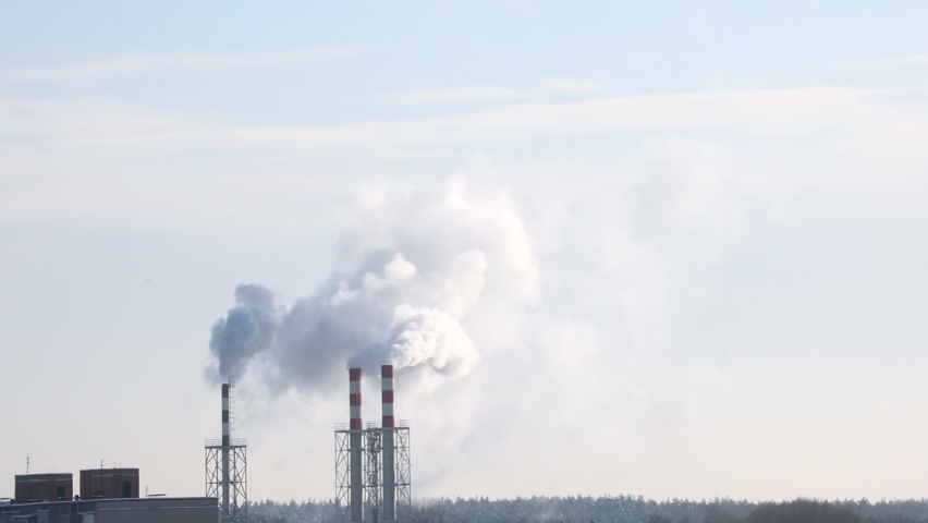 Smoke comes out of the chimney of the plant. Environmental pollution, gas emission, film grain | Shutterstock HD Video #1068287753