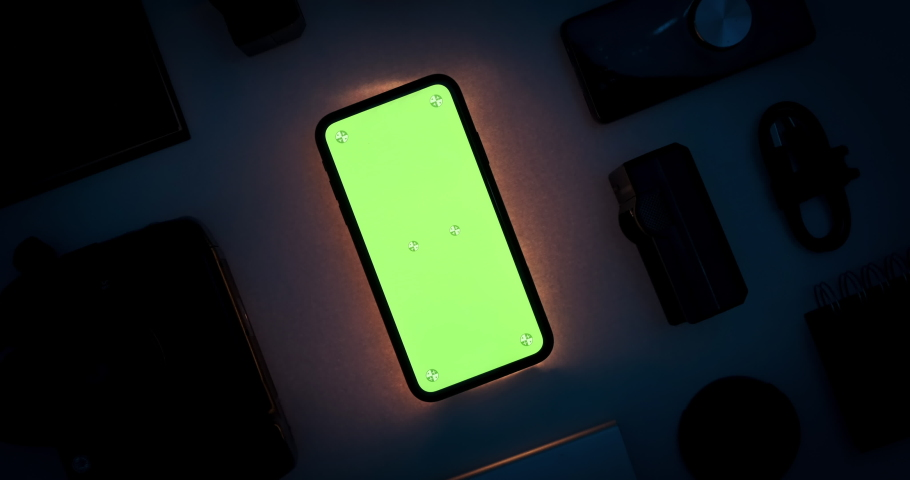 Phone chroma key green screen display mockup with tracking markers. Dark room interior with tech gadgets layout. Evening light scene with mobile illumination. Turning movement. 3D CGI close up 4k shot | Shutterstock HD Video #1068306968
