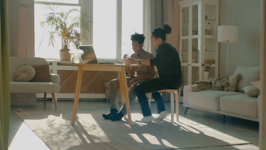 African American Black mother sits near her son, helping him with homework. Distance learning from home during COVID-19 coronavirus pandemic, stay home concept. Shot with 2x anamorphic lens | Shutterstock HD Video #1068307499
