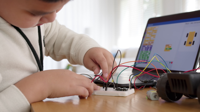 Young asia student remotely learn online at home in coding robot car and electronic board cable in STEM, STEAM, mathematics engineering science technology computer code in robotics for kids concept. Royalty-Free Stock Footage #1068352022