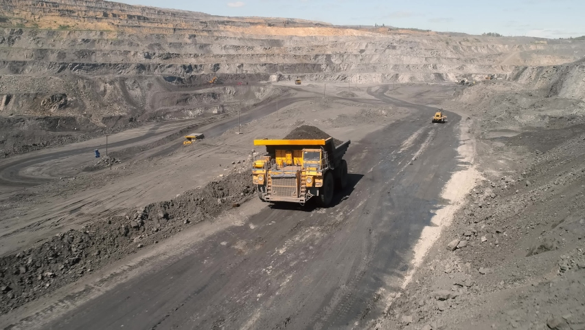 Large quarry dump truck. Loading rock in dumper. Loading coal into truck. Mining car machinery to transport coal. Open pit mine quarrying extractive industry stripping work. Big Yellow Mining Trucks