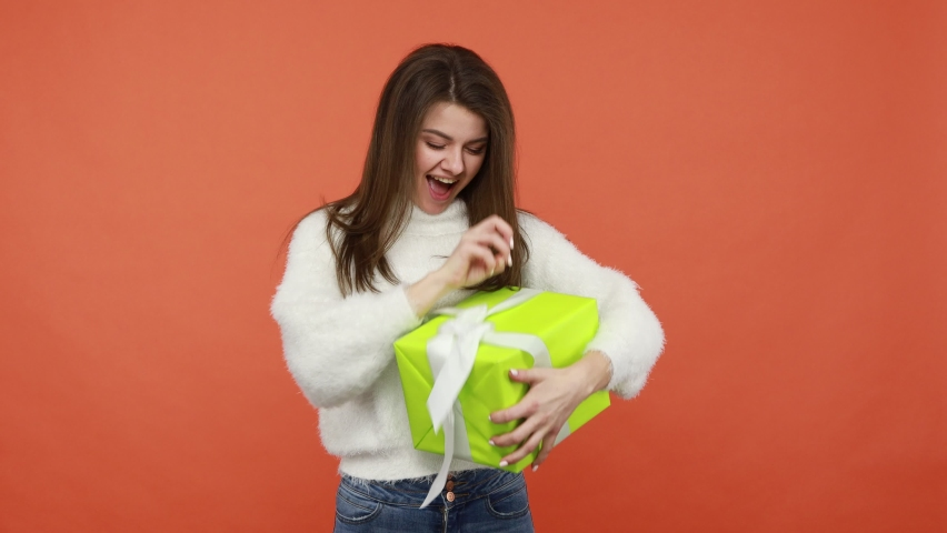 Happy excited brunette woman in white fluffy sweater rejoicing shaking big gift box, untying bow to peep inside, satisfied with present. Indoor studio shot isolated on orange background Royalty-Free Stock Footage #1068361892