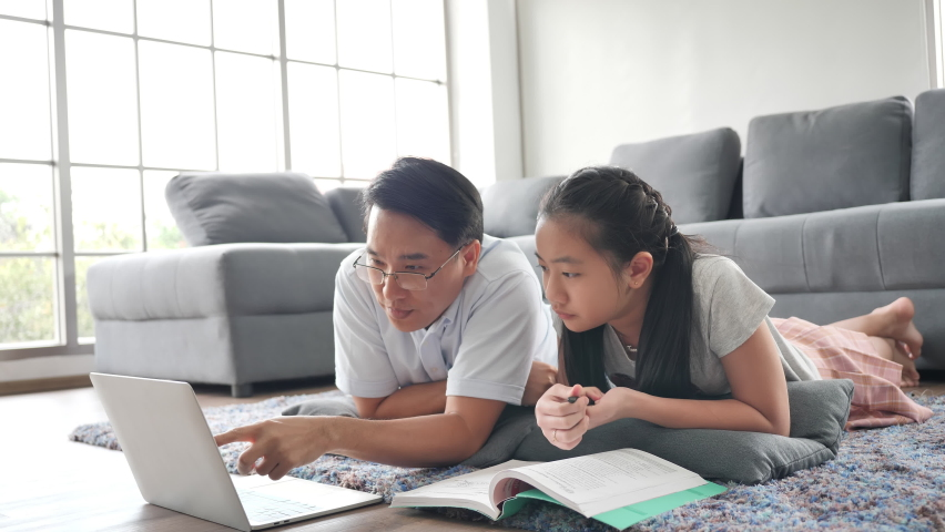 Asian family Father teaches daughter books by using laptop computer lying on the floor in the living room. Happy asian studying at home, study online | Shutterstock HD Video #1068371249