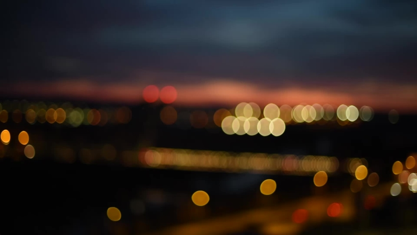 Night cityscape with bridge and sunset seen from the top of a mount. Blur and bokeh of night city lights. Hispanidad Bridge (Puente de la Hispanidad) in Valladolid, Spain.