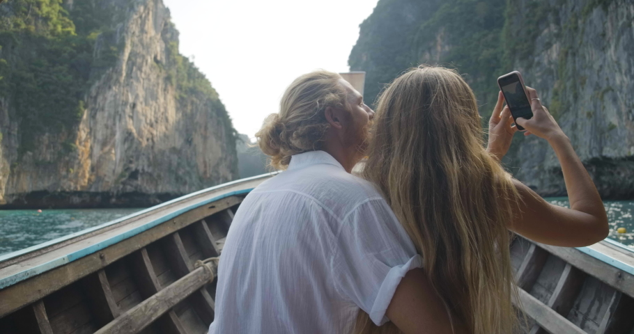 Romantic couple sitting on front of long tail boat seeing an amazing seascape of Phi Phi Islands and recording a video of beautiful view by smartphone during summer vacation travel in Phuket, Thailand | Shutterstock HD Video #1068376967