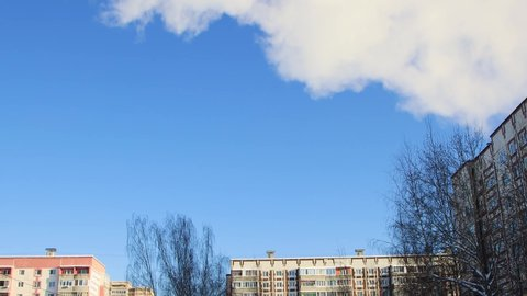 Fluffy, white cumulus clouds move smoothly and quickly over the house. Blue sky, beautiful cityscape on a sunny day. Nice background with clear weather. Slow motion time laps 4K video