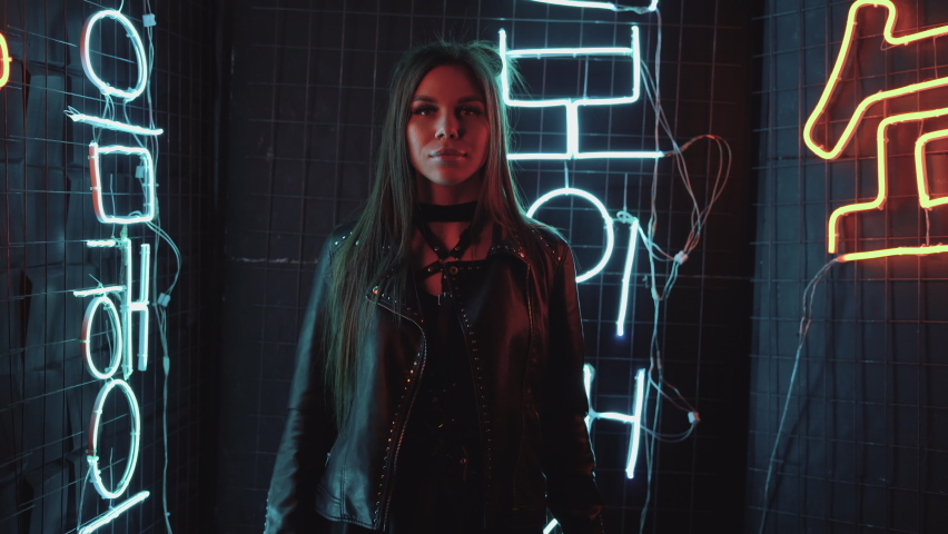 Stylish brunette girl in a leather jacket dances against the wall with light. Fashionable woman dancing single in the club. A hot girl with long hair is performing a modern dance. 4K footage   Shutterstock HD Video #1068390275