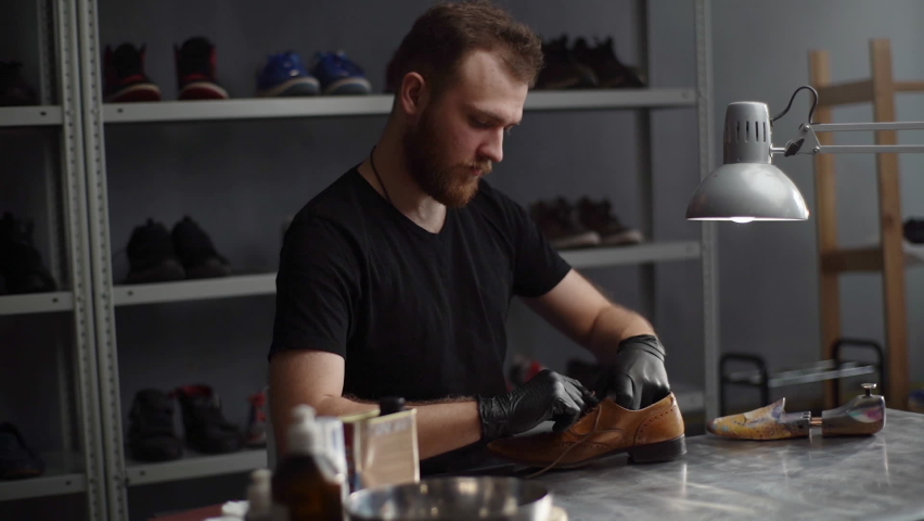 Hand held shot of shoemaker craftsman in gloves untying shoelaces on old worn light brown leather shoes to be repaired in dark craft shoe shop. Concept of cobbler artisan work. Shooting in slow motion Royalty-Free Stock Footage #1068394598
