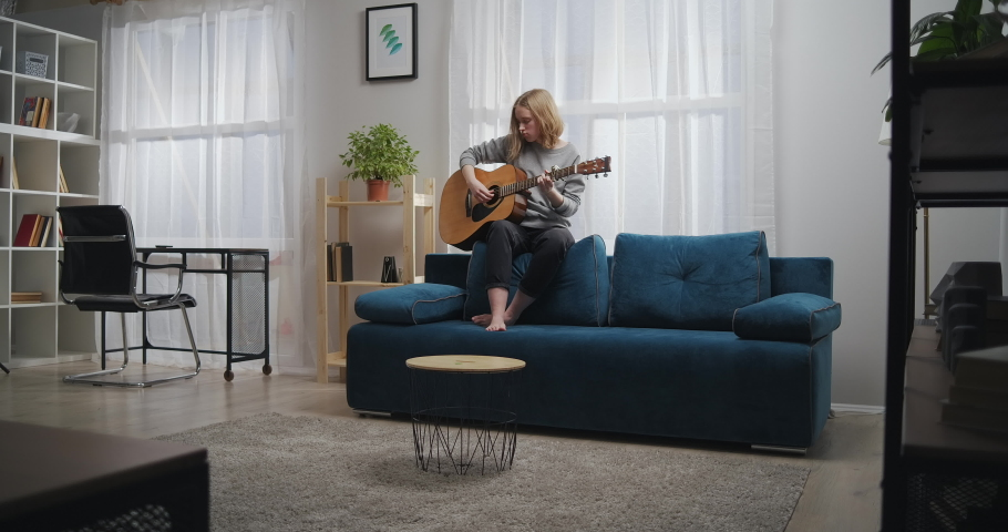 The girl plays the guitar on the back of the sofa. A woman composes music in a bright living room with beautiful light. The artist plays the classical guitar. A teenager trains on a musical instrument | Shutterstock HD Video #1068397859