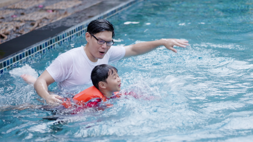 Asian family father is teaching and playing with his son swimming in pool. Swimming teacher training student to wear swimming life jacket. Happy holidays of summer. Concept Workout Royalty-Free Stock Footage #1068421043
