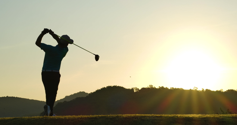 Slow Motion Golf Swing Drive Shot. Silhouette Asian male golfer enjoying vacation luxury resort using driver to tee off golf course fairway over sunset background.