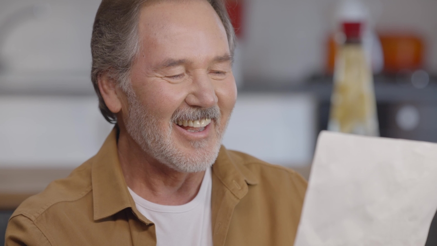 The old bearded man, laughing as he reads the letter in his hand, laughs when he reads funny things. Good news concept. Portrait of getting funny news. Royalty-Free Stock Footage #1068441149