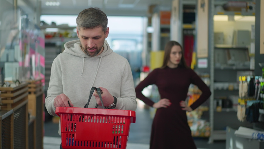 Portrait of satisfied Caucasian man looking at camera and smiling as irritated woman yelling and gesturing at background. Happy male shopper posing in hardware store with annoyed wife shouting.