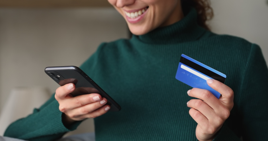 Close up female holds smartphone enters credit prepaid card data, makes easy instant payment, buying goods, fashion clothes, services using retail websites. Secure online purchase, spend money concept Royalty-Free Stock Footage #1068488795