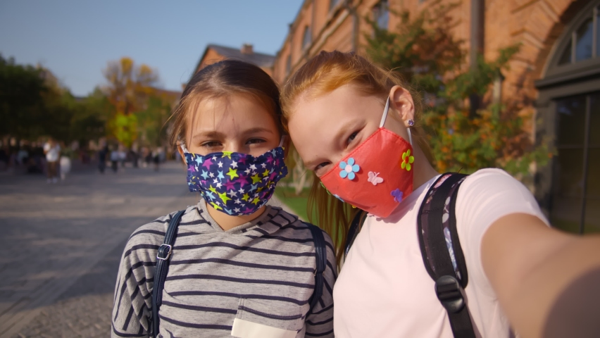 Cute schoolgirls in protective mask taking selfie outside school building. Pov shot of happy girls students wearing safety mask and taking photo together outdoors Royalty-Free Stock Footage #1068501548