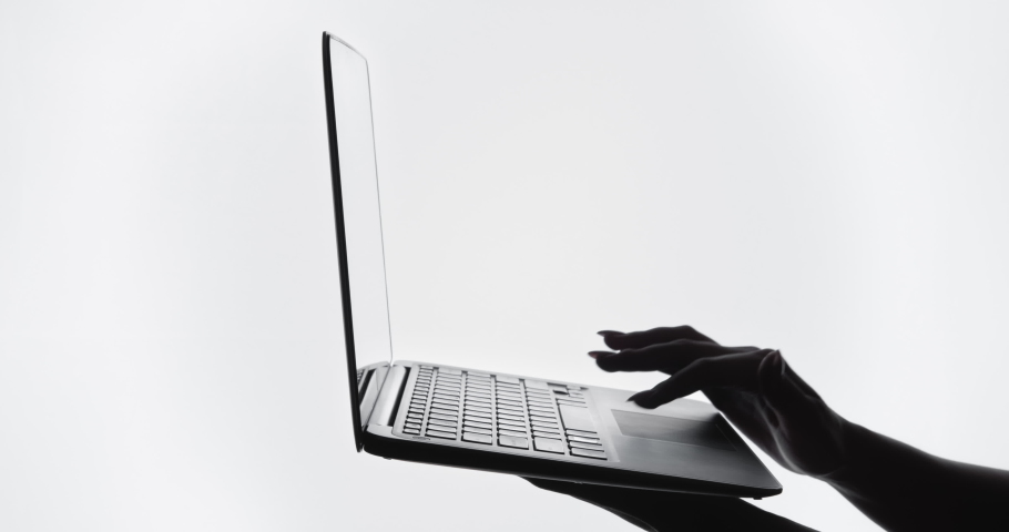 Remote job. Online business. Virtual office. Dark contrast silhouette of female freelancer hands using laptop for work isolated on white copy space background. | Shutterstock HD Video #1068503768