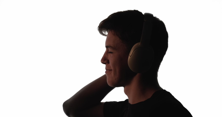 Male silhouette. Music relaxation. Positive lifestyle. Dark contrast profile outline of happy inspired guy enjoying listening audio in wireless headphones isolated on white empty space background. | Shutterstock HD Video #1068503777