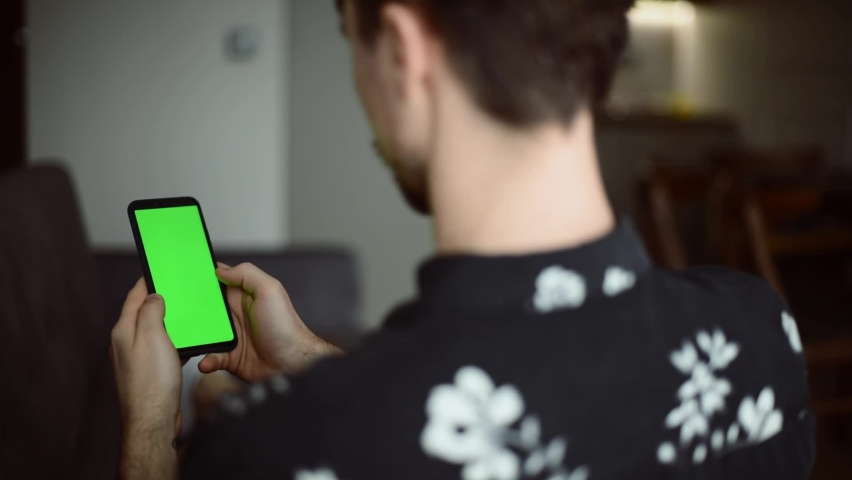 Man surfing in the internet watching content searching in the phone with green mock-up screen chroma key in the modern cozy home during the break on home office or weekend. | Shutterstock HD Video #1068504764