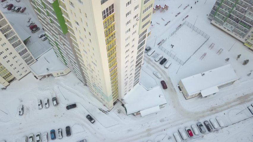 Drone aerial view of the courtyard and parking lot of a high-rise residential building. Snow-covered cars and streets in the city in winter.