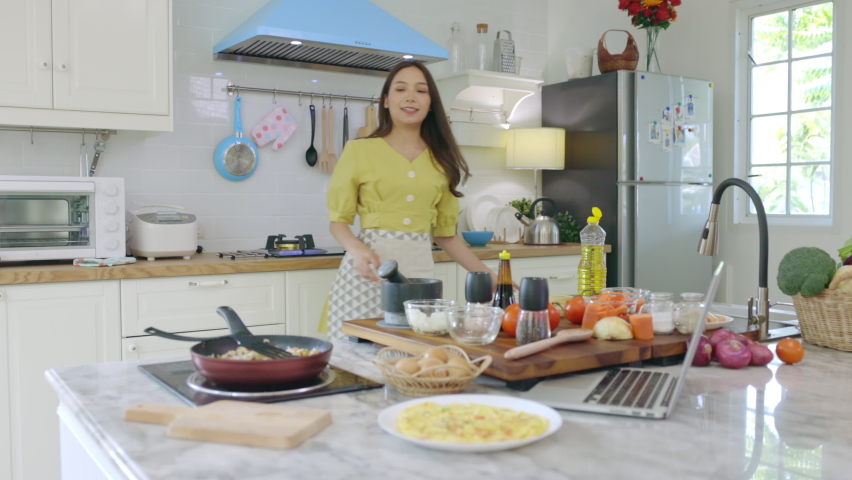 A beautiful Asian girl makes breakfast by looking at how to make it with her laptop computer with a happy face. At her own house | Shutterstock HD Video #1068527561