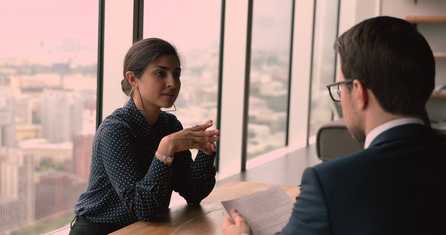 Confident beautiful young indian mixed race woman answering questions about job experience, passing job interview with skilled male caucasian human resources manager employer at office meeting. Royalty-Free Stock Footage #1068547958