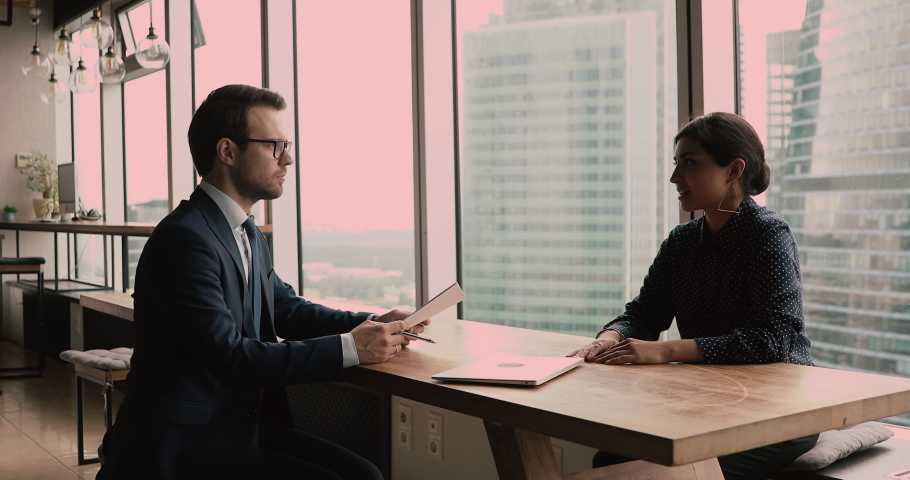 Confident 30s male hr manager in formal wear examining professional skills of young indian ethnicity female seeker, involved in hiring interview in modern skyscraper office, discussing job offer. Royalty-Free Stock Footage #1068547979