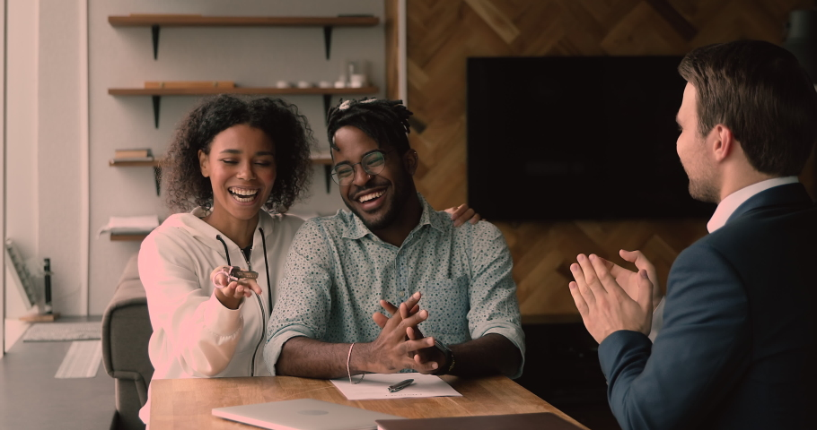 Happy young african american couple meeting male real estate agent in office, signing contract, feeling excited of purchasing new own apartment or house, shaking hands celebrating closing deal. Royalty-Free Stock Footage #1068548006