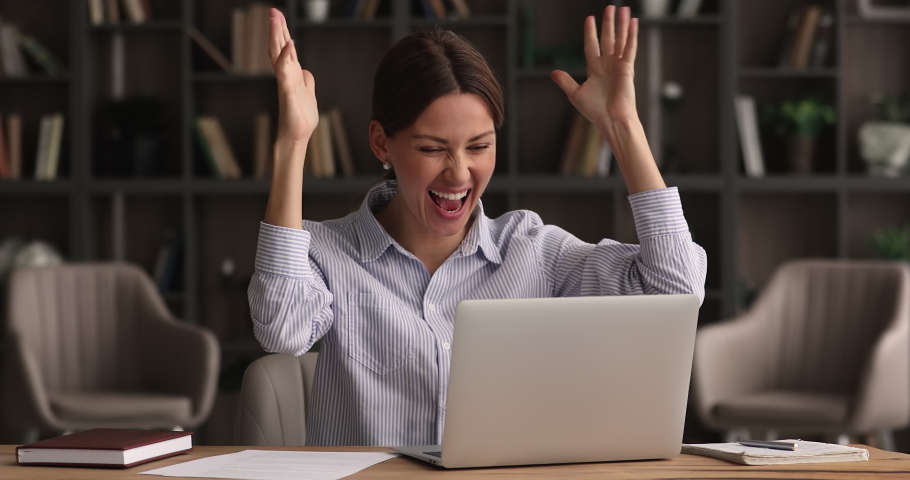 Concentrated young 35s beautiful business lady looking at computer screen, reading email carefully, feeling excited of getting good news, celebrating receiving bank loan confirmation or online success