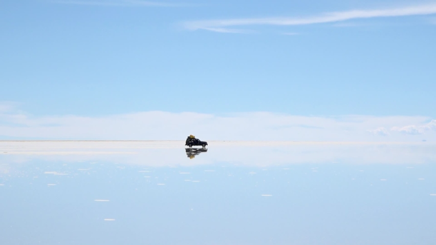 Panorama of Uyuni Salt Flats in Bolivia. Salt flat desert is covered by water in wet season. Reflections of cars and mountains at big distance.