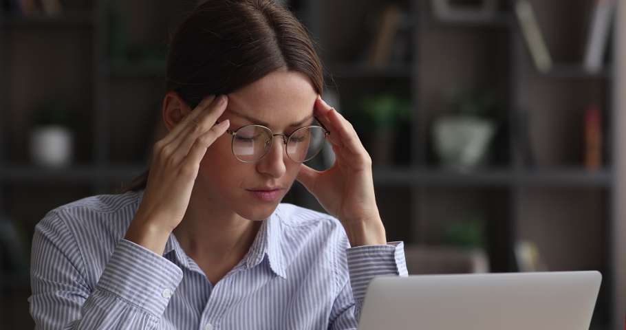 Close up head shot stressed overwhelmed young caucasian businesswoman in eyeglasses massaging temples, feeling exhausted, suffering from headache due to computer overwork, workaholic people concept. | Shutterstock HD Video #1068565637