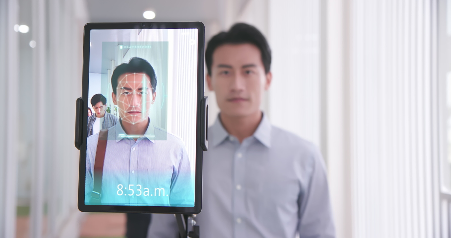 Facial recognition concept - Asian businessman using face scanner to clock in work and check body temperature | Shutterstock HD Video #1068614387