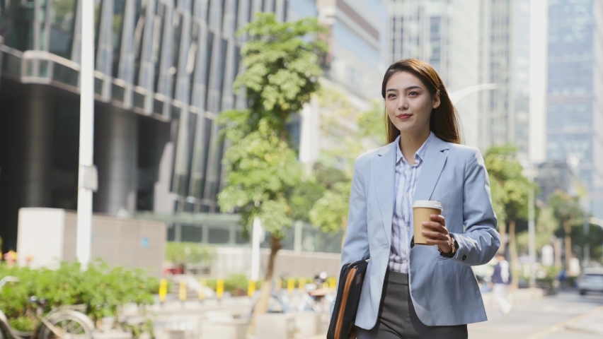 successful young asian woman walking in central business district  in modern city Royalty-Free Stock Footage #1068615752