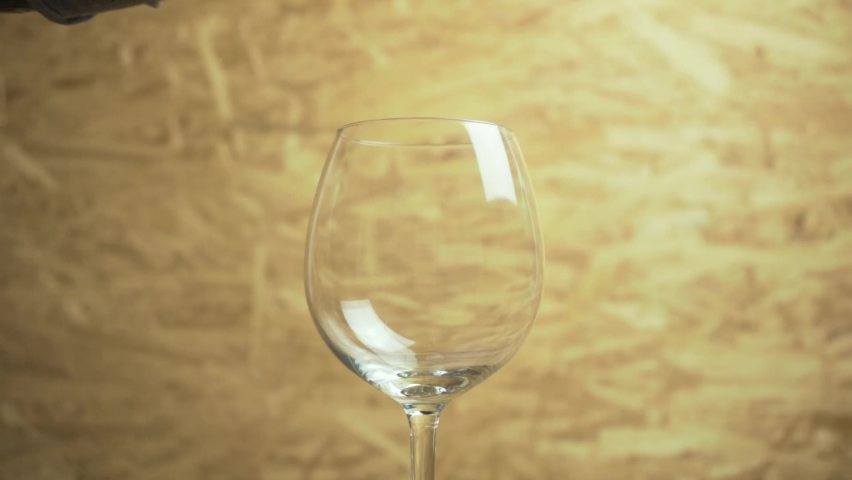 Red wine is being poured into a wine glass.   Shutterstock HD Video #1068620033