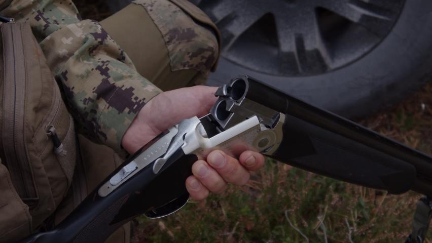 Hands insert cartridges in double barrel of shotgun. Slow-motion   Shutterstock HD Video #1068620531