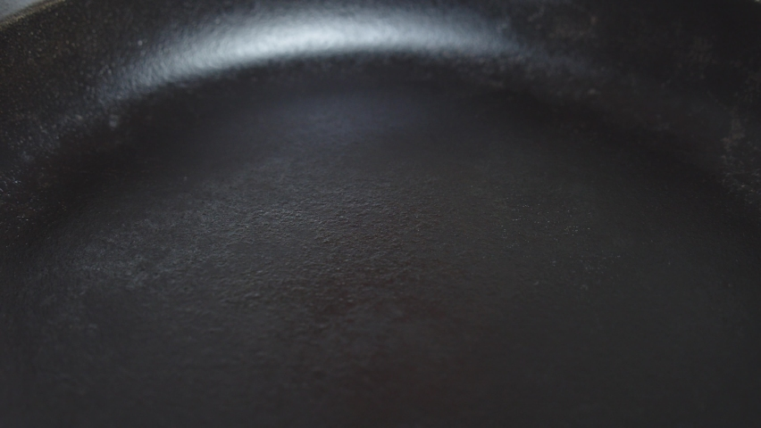 Adding oil onto hot frying pan. Slow motion, close up shot.   Shutterstock HD Video #1068620561